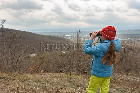 a girl examines a mountain landscape