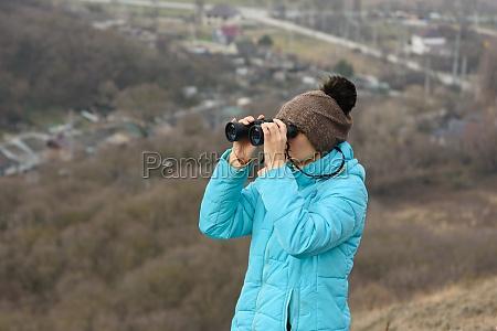 girl looking through binoculars while standing
