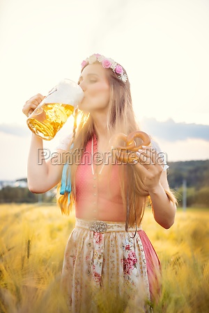 woman in traditional clothing drinking beer