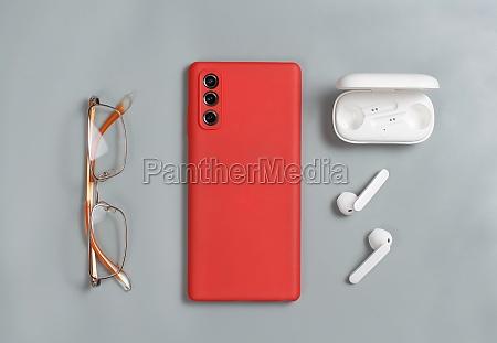 smartphone glasses and white wireless earphones