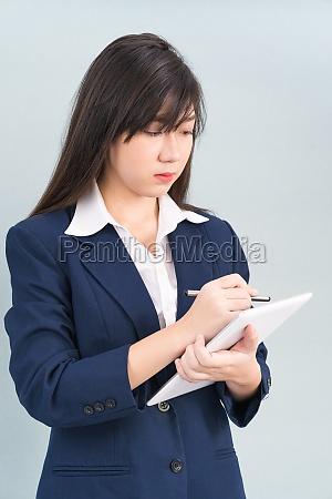 woman in suit using digital tablet