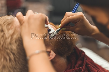 barber woman shaves beard with a
