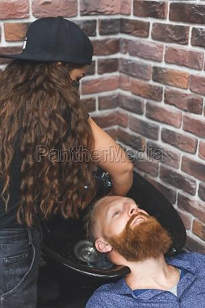 barber woman washes customer man head