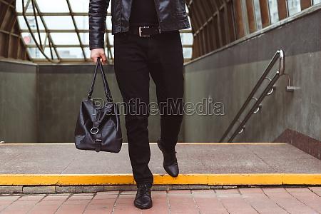 fashionably dressed man walks from underground