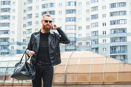 fashionably dressed bearded caucasian man walks