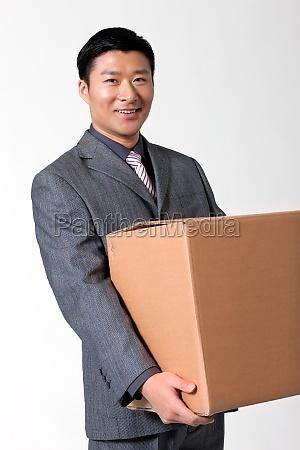 a white collar man carrying cardboard