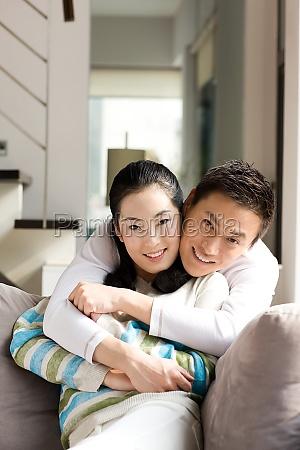 hugs adult oriental face the camera