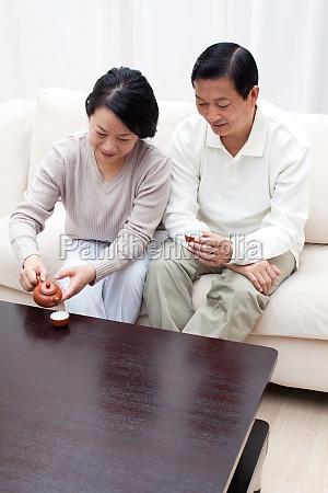 family sitting teapot older woman two