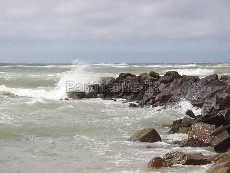 solid breakwater rocks with cloudy ocean