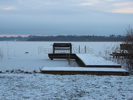 bathing pier with bench in winter