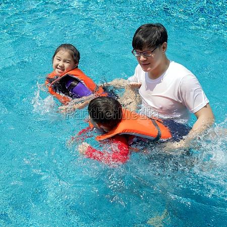 an asian father teaches his son