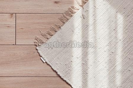 wicker beige rug on wooden parquet