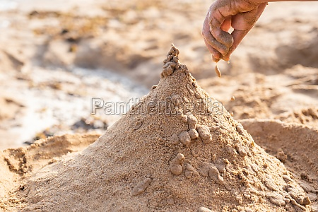 child hands making sand towers on