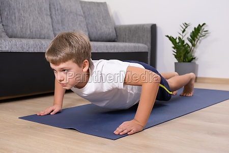 boy on yoga mat at home