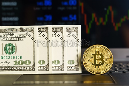 bitcoins coin and banknotes on keyboard