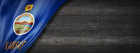 kansas flag on black wood wall