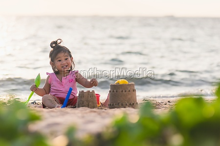 cute little girl playing sand with
