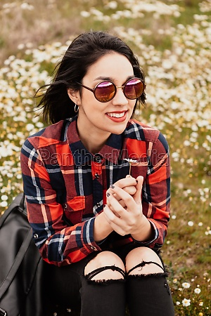 beautiful woman smelling a daisy