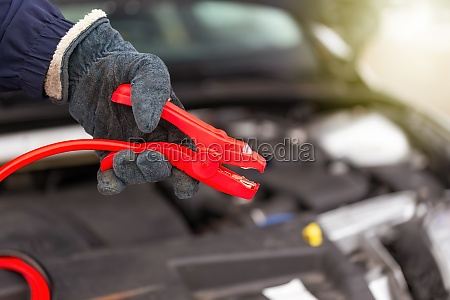 person holding red jumper cable next