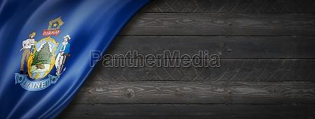 maine flag on black wood wall