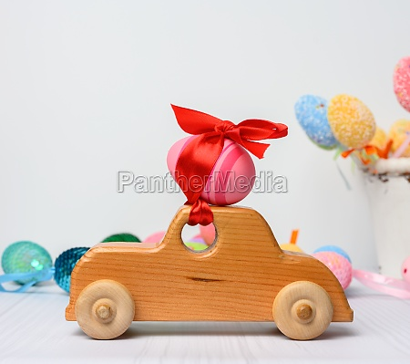 wooden toy car carrying a pink