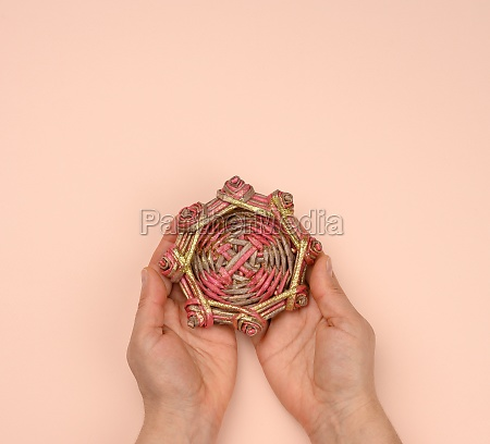 two female hands holding a wicker