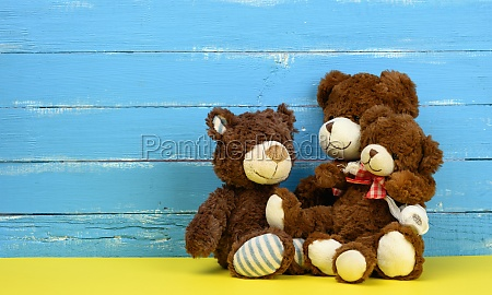 teddy bears sitting on a yellow