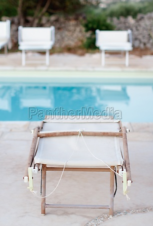 folded deck chairs near a swimming