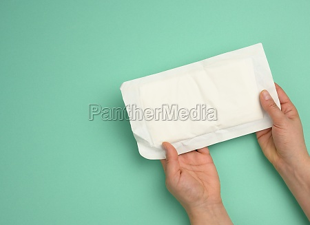 two female hands hold white paper
