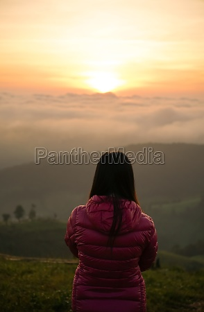 woman watching sunrise at hilltop