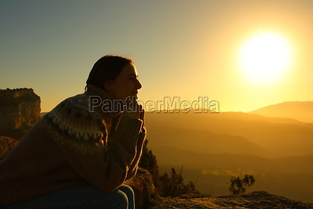woman silhouette meditating at sunset in