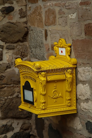 an old yellow cast iron mailbox