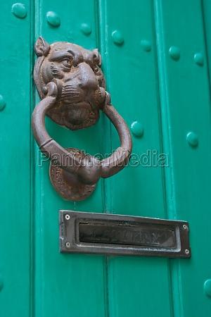 green door with lion door knocker