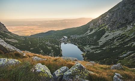 mountain lake at sunset with rocks