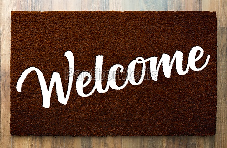 dark brown welcome mat on wood