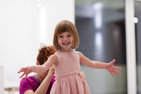 young mother helping daughter while putting