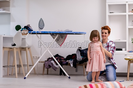 mother helping daughter while putting on
