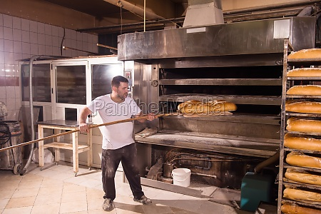 bakery worker taking out freshly baked