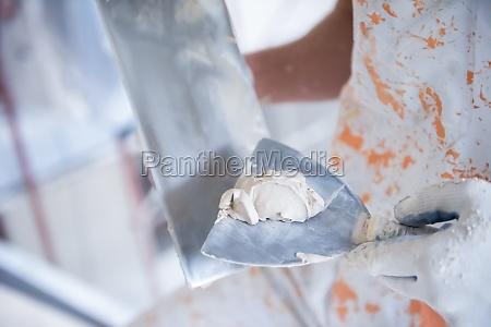 construction worker plastering on gypsum walls