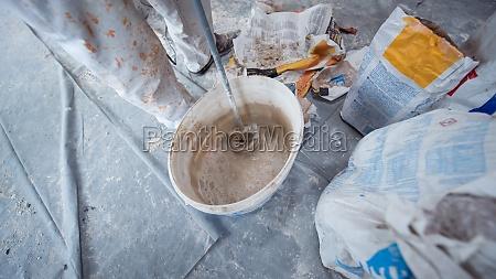 construction worker mixing plaster in bucket