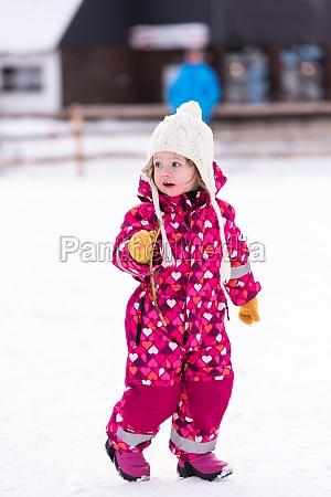 little girl having fun at snowy