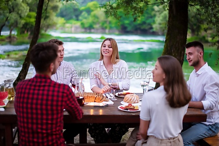 happy friends having picnic french dinner