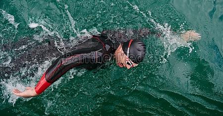 triathlon athlete swimming on lake wearing