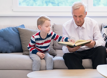 modern muslim grandfather with grandson reading