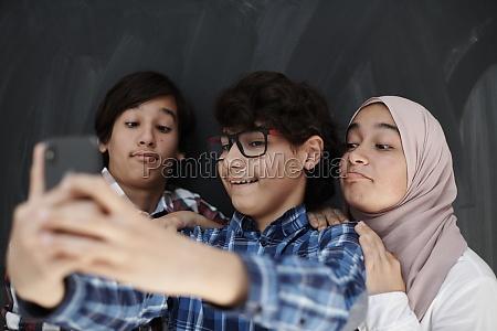group of arab teens taking selfie