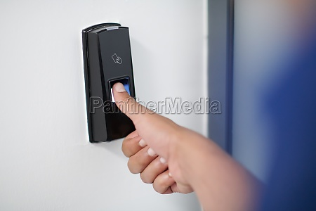 man pressing fingerprint scanner