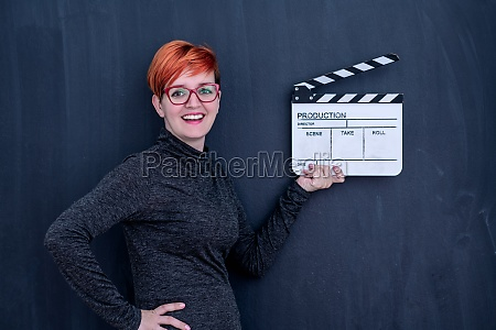 redhead woman holding movie clapper