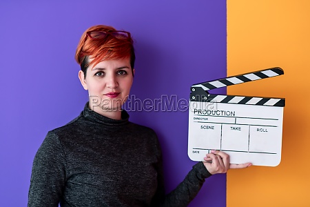 woman holding movie clapper against colorful