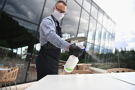 waiter cleaning the table with disinfectant