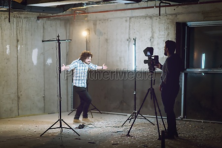 videographer recording casual businessman in front